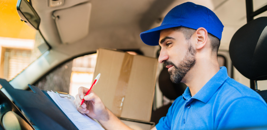 Delivery man checking a list inside his van