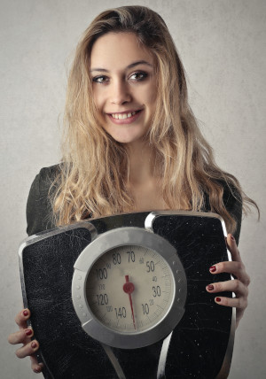 Girl holding a weighting scale