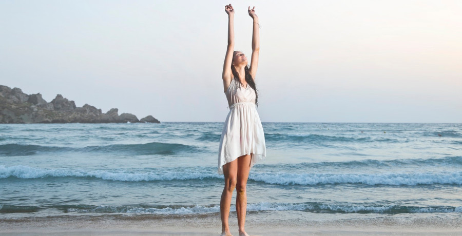 A woman raising her arms in a summer suit while on the beach