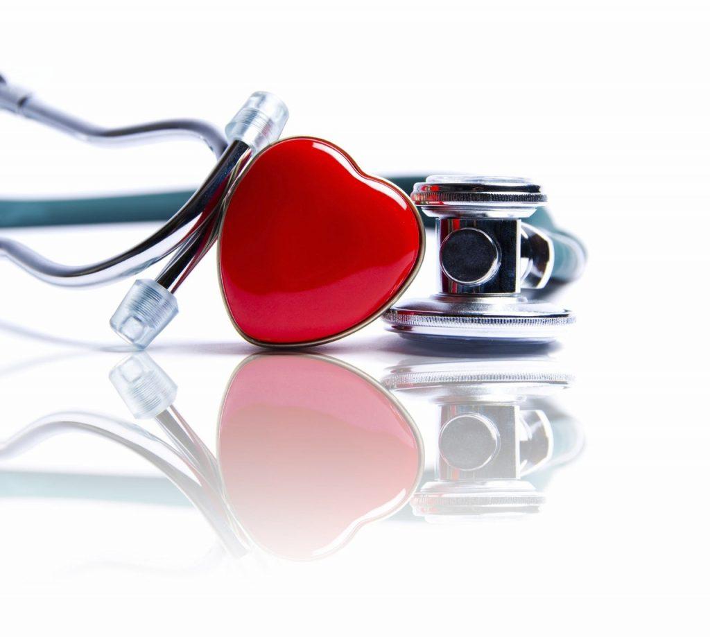 A heart shaped pin beside a stethoscope