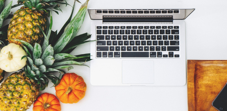 Laptop on a table with fruits and vegetables