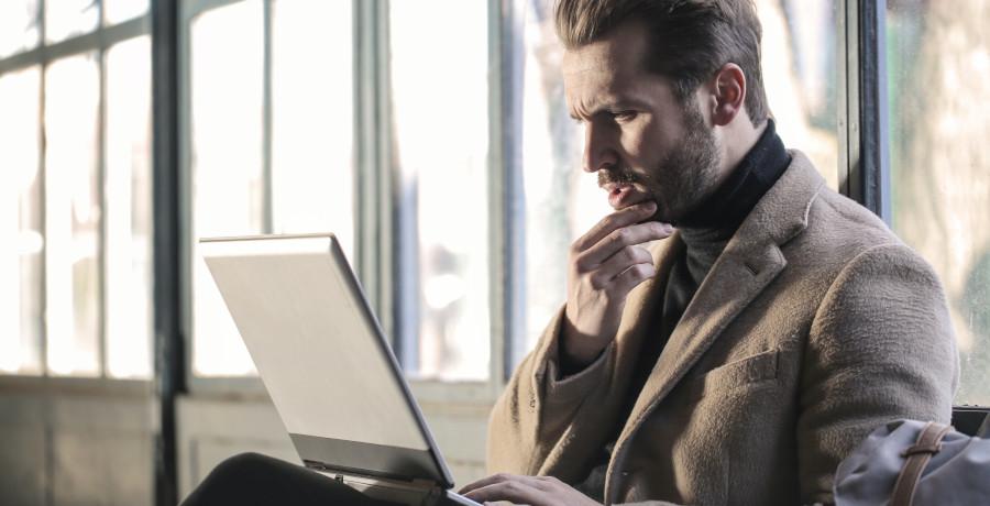 Man using laptop looking shocked
