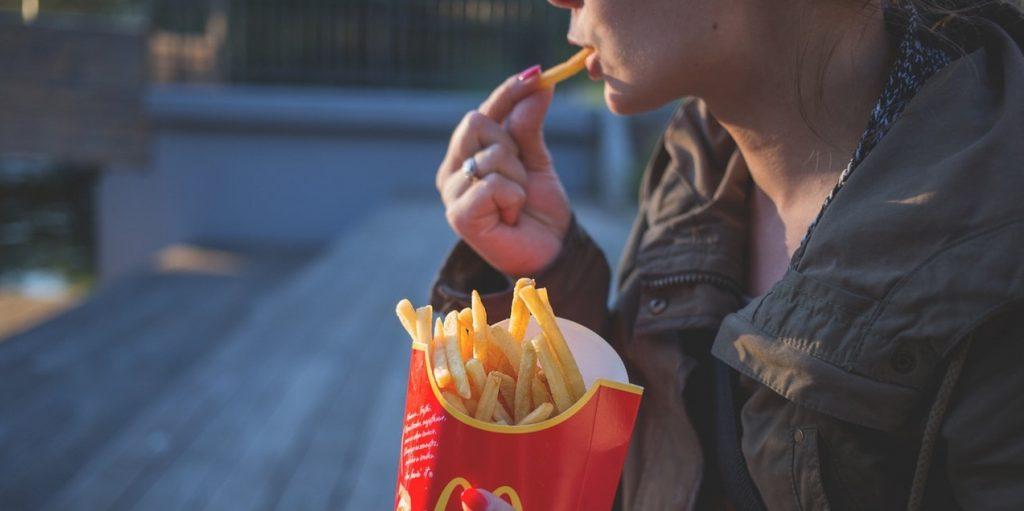 Woman eating fried potatoes