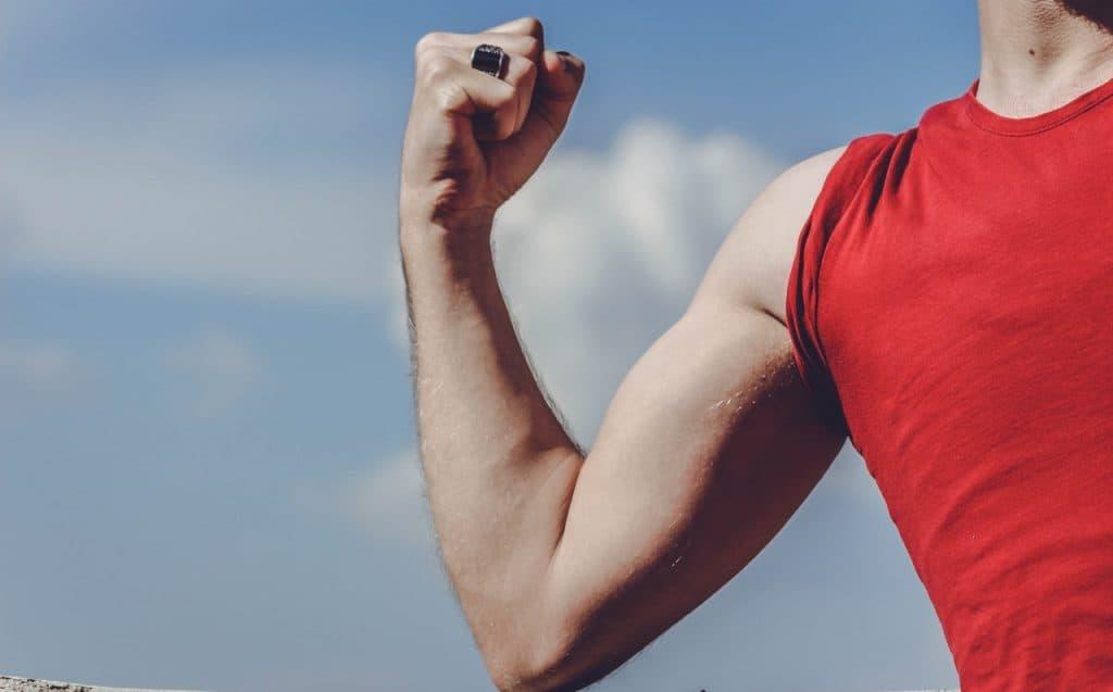 Muscled man raising arm