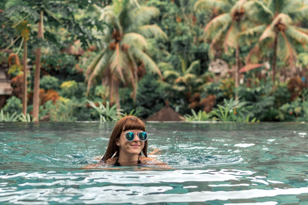 A woman swimming with sunglasses on