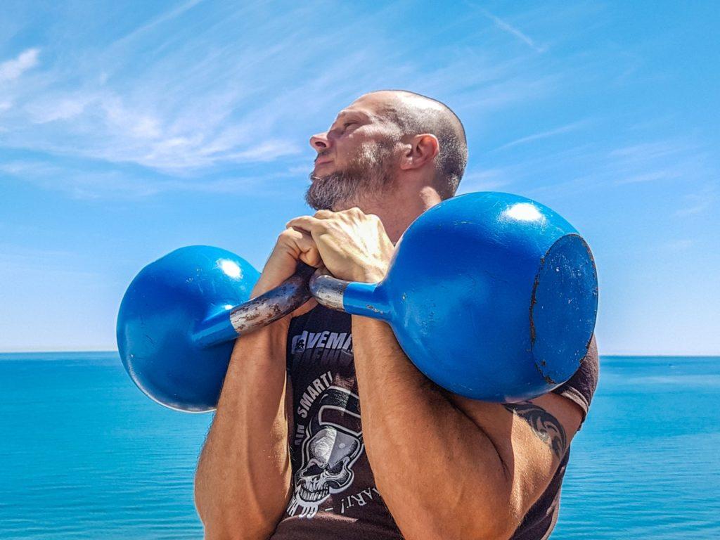 Bald man carrying blue kettle weights