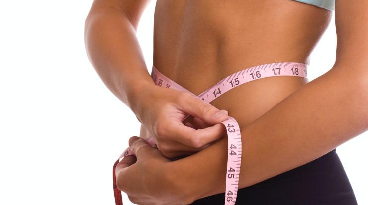 Slim woman using a measuring tape