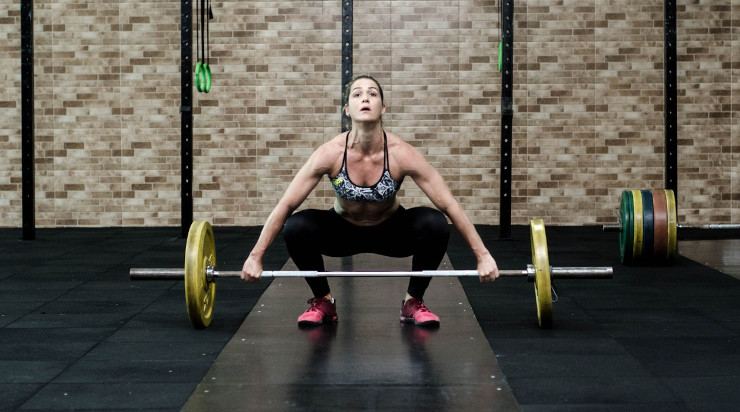 Woman lifting bars in a gym