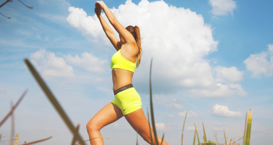 Fit woman doing workout on an open field