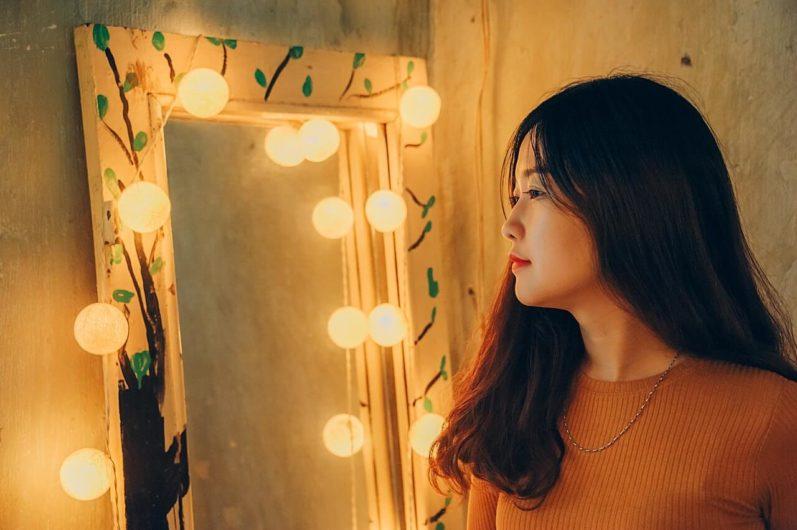 Woman facing the lit mirror