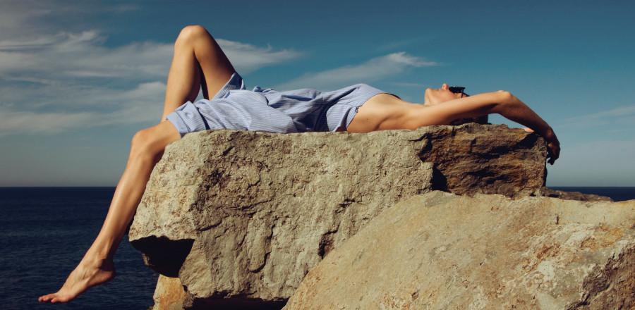 Woman lying down on a rock beside the sea